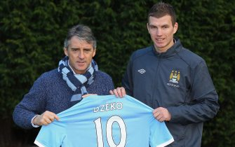 MANCHESTER, ENGLAND - JANUARY 11:  Edin Dzeko the new signing for Manchester City poses with Roberto Mancini the manager of Manchester City during a photocall at the Carrington Training Complex on January 11, 2011 in Manchester, England.  (Photo by Alex Livesey/Getty Images)