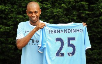 epa03782716 Manchester City's new Brazilian midfielder Fernandinho poses for photographers with his new jersey during a press conference of the English Premier League soccer club at Carrington training ground in Manchester, Britain, 10 July 2013.  EPA/PETER POWELL