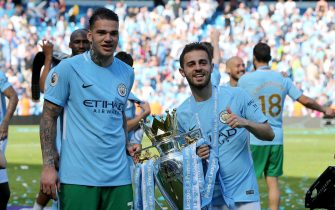 epa06716247 Manchester City's Bernado Silva (R) and Ederson Moraes (L) hold the Premier League trophy following the English Premier League soccer match between Manchester City and Huddersfield Town at the Etihad Stadium in Manchester, Britain, 06 May 2018.  EPA/NIGEL RODDIS EDITORIAL USE ONLY. No use with unauthorised audio, video, data, fixture lists, club/league logos 'live' services. Online in-match use limited to 75 images, no video emulation. No use in betting, games or single club/league/player publications.