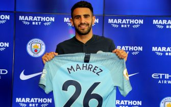 New Manchester City signing Riyad Mahrez holds up his shirt during the press conference at the City Football Academy, Manchester. (Photo by Richard Sellers/PA Images via Getty Images)