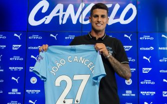Manchester City's newly signed Portuguese defender Joao Cancelo poses with his club shirt during his unveiling at the City Football Academy in Manchester on August 8, 2019. (Photo by OLI SCARFF / AFP)        (Photo credit should read OLI SCARFF/AFP via Getty Images)