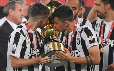 TOPSHOT - Juventus midfielder from Italy Miralem Pjanic and Juventus' forward from Argentina Paulo Dybala (R) kiss the trophy after winning the Italian Tim Cup (Coppa Italia) final Juventus vs AC Milan at the Olympic stadium on May 9, 2018 in Rome. - Juventus crushed AC Milan 4-0 on today at the Stadio Olimpico to win a fourth consecutive Italian Cup. Mehdi Benatia opened the floodgates after 56 minutes for the first of a double of the night for the Moroccan with Douglas Costa also finding the net in the space of nine minutes. A Nikola Kalinic own goal accounted for the fourth (Photo by Tiziana FABI / AFP)        (Photo credit should read TIZIANA FABI/AFP via Getty Images)
