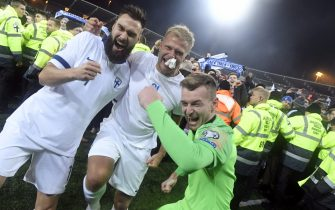 Finnish captain Tim Sparv (L) celebrates with Paulus Arajuuri and goalkeeper Lukas Hradecky after the UEFA Euro 2020 Group J qualification football match between Finland and Liechtenstein in Helsinki, Finland, on November 15, 2019. - Finland has qualified for the first time for a major football tournament. (Photo by Markku Ulander / Lehtikuva / AFP) / Finland OUT (Photo by MARKKU ULANDER/Lehtikuva/AFP via Getty Images)