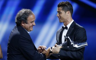 Real Madrid's Portuguese forward Cristiano Ronaldo (R) shakes hands with UEFA President Michel Platini, after Ronaldo won the UEFA European Player of the Year trophy, on August 28, 2014 in Monaco, after the draw for the 2014/2015 European Champions League group stages. AFP PHOTO / VALERY HACHE        (Photo credit should read VALERY HACHE/AFP via Getty Images)