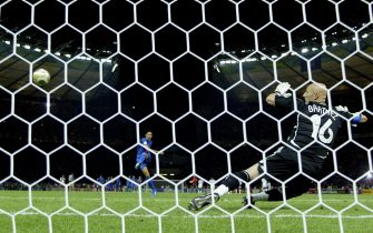 BERLIN - JULY 09:  Fabio Grosso (L) of Italy takes the matchwinning penalty, as Goalkeeper Fabien Barthez (R) of France dives the wrong way during the FIFA World Cup Germany 2006 Final match between Italy and France at the Olympic Stadium on July 9, 2006 in Berlin, Germany.  (Photo by Michael Steele/Getty Images)