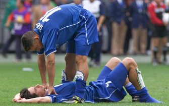 Italian forward Roberto Baggio (up) comforts team-mate Demetrio Albertini 03 July 1998 after the penalty shoot-out of the 1998 Soccer World Cup quarter-final match between France and Italy at the Stade de France in Saint-Denis, near to Paris. 