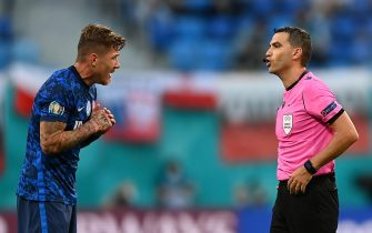epa09271046 Juraj Kucka (L) of Slovakia talks to Romanian referee Ovidiu Hategan during the UEFA EURO 2020 group E preliminary round soccer match between Poland and Slovakia in St. Petersburg, Russia, 14 June 2021.  EPA/Kirill Kudryavtsev / POOL (RESTRICTIONS: For editorial news reporting purposes only. Images must appear as still images and must not emulate match action video footage. Photographs published in online publications shall have an interval of at least 20 seconds between the posting.)