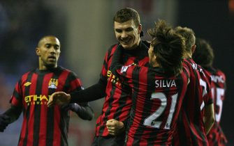 epa03062868 Manchester City's Edin Dzeko (C) celebrates with his teammates after scoring the opening goal against Wigan during their English Premier League soccer match in Wigan, north west Britain, 16 January 2012.  EPA/LINDSEY PARNABY DataCo terms and conditions apply http//www.epa.eu/downloads/DataCo-TCs.pdf