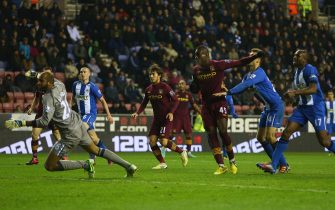 WIGAN, ENGLAND - NOVEMBER 28:  Mario Balotelli (3R) of Manchester City  scores his sides opening goal during the Barclays Premier League match between Wigan Athletic and Manchester City at the DW Stadium on November 28, 2012 in Wigan, England.  (Photo by Michael Steele/Getty Images)