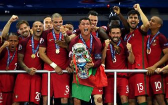 PARIS, FRANCE - JULY 10:  Cristiano Ronaldo of Portugal (c) lifts the European Championship trophy after his side win 1-0 against France during the UEFA EURO 2016 Final match between Portugal and France at Stade de France on July 10, 2016 in Paris, France.  (Photo by Matthias Hangst/Getty Images)
