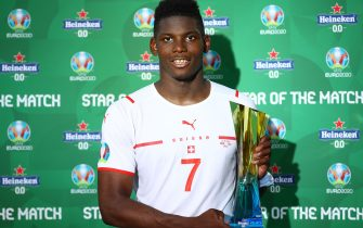 """BAKU, AZERBAIJAN - JUNE 12: Breel Embolo of Switzerland poses for a photograph with their Heineken """"Star of the Match"""" award after the UEFA Euro 2020 Championship Group A match between Wales and Switzerland at the Baku Olympic Stadium on June 12, 2021 in Baku, Azerbaijan. (Photo by Matthew Lewis - UEFA/UEFA via Getty Images)"""