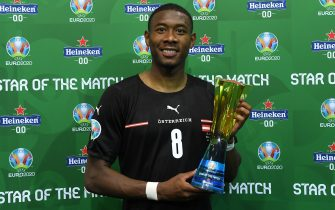 """BUCHAREST, ROMANIA - JUNE 13: David Alaba of Austria poses for a photograph with their Heineken """"Star of the Match"""" award after the UEFA Euro 2020 Championship Group C match between Austria and North Macedonia at National Arena Bucharest on June 13, 2021 in Bucharest, Romania. (Photo by Alex Caparros - UEFA/UEFA via Getty Images)"""