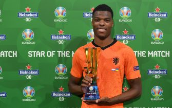 """AMSTERDAM, NETHERLANDS - JUNE 13: Denzel Dumfries of Netherlands poses for a photograph with their Heineken """"Star of the Match"""" award after the UEFA Euro 2020 Championship Group C match between Netherlands and Ukraine at the Johan Cruijff ArenA on June 13, 2021 in Amsterdam, Netherlands. (Photo by Lukas Schulze - UEFA/UEFA via Getty Images)"""