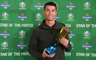 """BUDAPEST, HUNGARY - JUNE 15: Cristiano Ronaldo of Portugal poses for a photograph with their Heineken """"Star of the Match"""" award after the UEFA Euro 2020 Championship Group F match between Hungary and Portugal at Puskas Arena on June 15, 2021 in Budapest, Hungary. (Photo by Angel Martinez - UEFA/UEFA via Getty Images)"""