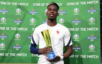 """MUNICH, GERMANY - JUNE 15: Paul Pogba of France poses for a photograph with their Heineken """"Star of the Match"""" award after the UEFA Euro 2020 Championship Group F match between France and Germany at Football Arena Munich on June 15, 2021 in Munich, Germany. (Photo by Sebastian Widmann - UEFA/UEFA via Getty Images)"""