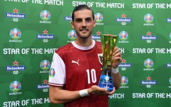 """BUCHAREST, ROMANIA - JUNE 21: Florian Grillitsch of Austria poses for a photograph with their Heineken """"Star of the Match"""" award after the UEFA Euro 2020 Championship Group C match between Ukraine and Austria at National Arena on June 21, 2021 in Bucharest, Romania. (Photo by Alex Caparros - UEFA/UEFA via Getty Images)"""