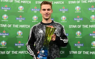 """MUNICH, GERMANY - JUNE 23: Joshua Kimmich of Germany poses for a photograph with their Heineken """"Star of the Match"""" award after the UEFA Euro 2020 Championship Group F match between Germany and Hungary at Allianz Arena on June 23, 2021 in Munich, Germany. (Photo by Sebastian Widmann - UEFA/UEFA via Getty Images)"""