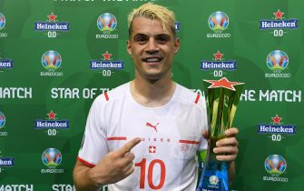 """BUCHAREST, ROMANIA - JUNE 28: Granit Xhaka of Switzerland poses for a photograph with their Heineken """"Star of the Match"""" award after the UEFA Euro 2020 Championship Round of 16 match between France and Switzerland at National Arena on June 28, 2021 in Bucharest, Romania. (Photo by Alex Caparros - UEFA/UEFA via Getty Images)"""