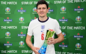 """LONDON, ENGLAND - JUNE 29: Harry Maguire of England poses for a photograph with their Heineken """"Star of the Match"""" award after the UEFA Euro 2020 Championship Round of 16 match between England and Germany at Wembley Stadium on June 29, 2021 in London, England. (Photo by Shaun Botterill - UEFA/UEFA via Getty Images)"""