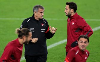 epa08725090 Turkey's head coach Senol Guenes (L) and Turkey's Hakan Calhanoglu (R) attend a training session at the Rheinenergiestadion in Cologne, Germany, 06 October 2020. Turkey will face Germany in an international friendly soccer match on 07 October 2020 in Cologne. The city of Cologne has decided that the international match of the German national team against Turkey may take place with a maximum of 300 spectators due to the increased number of corona virus infections.  EPA/FRIEDEMANN VOGEL