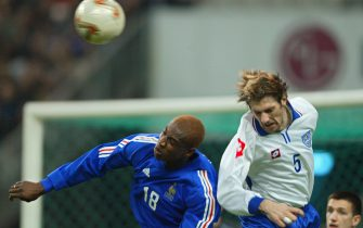 French midfielder Olivier Kapo (L) and Yugoslav defender Mladen Krstajic jump for an aerial ball as French midfielder Eric Carrière looks on during the France/Yugoslavia friendly soccer game 20 November 2002 at the Stade de France in Saint-Denis near Paris. (Photo by Patrick HERTZOG / AFP) (Photo by PATRICK HERTZOG/AFP via Getty Images)