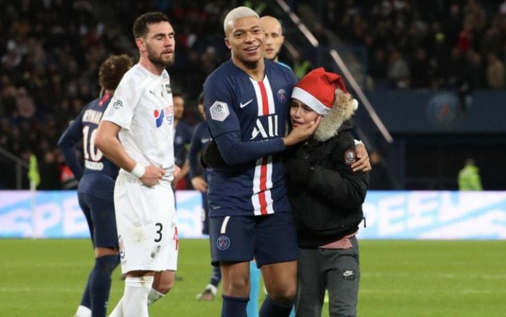 Mbappé abbraccia un giovanissimo invasore