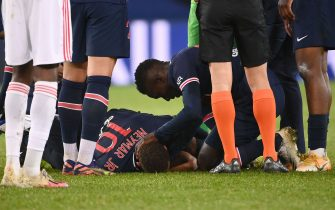 Paris Saint-Germain's Brazilian forward Neymar (C) is assisted by teammates after getting injured during the French L1 football match between Paris Saint-Germain (PSG) and Lyon (OL), on December 13, 2020 at the Parc des Princes stadium in Paris. (Photo by FRANCK FIFE / AFP) (Photo by FRANCK FIFE/AFP via Getty Images)
