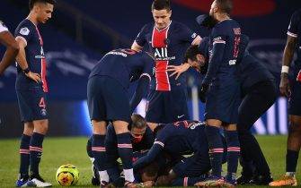 Paris Saint-Germain's Brazilian forward Neymar (C, down) is assisted by teammates after getting injured during the French L1 football match between Paris Saint-Germain (PSG) and Lyon (OL), on December 13, 2020 at the Parc des Princes stadium in Paris. (Photo by FRANCK FIFE / AFP) (Photo by FRANCK FIFE/AFP via Getty Images)