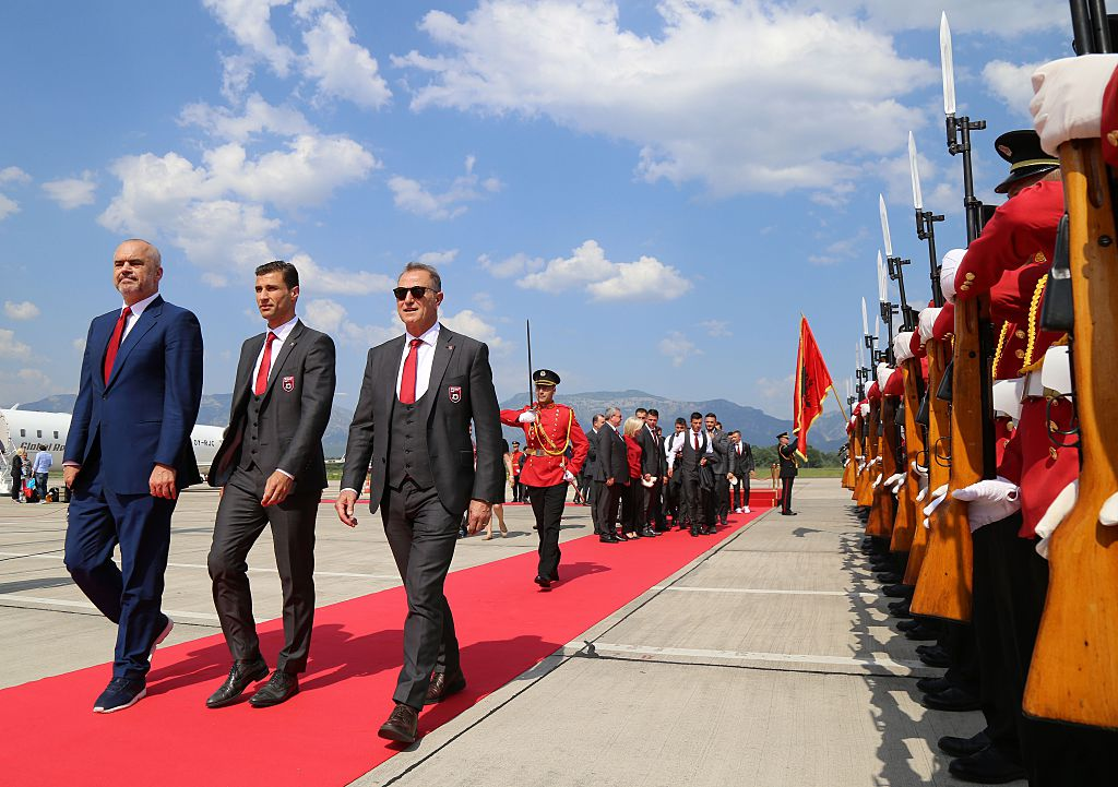 Albanian Prime Minister Edi Rama (L), the captain of Albania's national soccer team, Lorik Cana (C) and Albania's national football team head coach Gianni De Biasi review an honor guard during a welcoming ceremony at Mother Teresa airport in Tirana on June 23, 2016.  Albania's Euro 2016 squad was welcomed home on June 23 with a formal red-carpet ceremony and National Guard troops on its return from the country's first ever participation at a European Championship. / AFP / GENT SHKULLAKU        (Photo credit should read GENT SHKULLAKU/AFP via Getty Images)