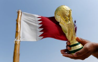 DOHA, QATAR - January 25 : A general view of a replica of the FIFA World Cup Trophy by the national flag of Qatar at the Al Zubara Fort, a UNESCO World Heritage Site, in Madinat ash Shamal, Qatar Al Zubara fort in the North of Qatar, the host country of the Qatar 2022 FIFA World Cup on January 25 2016 in Doha, Qatar. (Photo by Matthew Ashton - AMA/Getty Images)