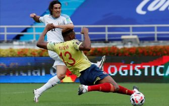 epa08818999 Edinson Cavani (L) of Uruguay scores next to Yerry Mina of Colombia during the South American qualifiers soccer match to Qatar 2022 World Cup between Colombia and Uruguay at Metropolitano in Barranquilla, Colombia, 13 November 2020.  EPA/MAURICIO DUENAS CASTANEDA