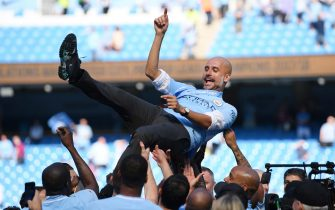 MANCHESTER, ENGLAND - MAY 06:  Josep Guardiola, Manager of Manchester City is thrown into the air as he and his team celebrate winning the premier league after the Premier League match between Manchester City and Huddersfield Town at Etihad Stadium on May 6, 2018 in Manchester, England.  (Photo by Shaun Botterill/Getty Images)