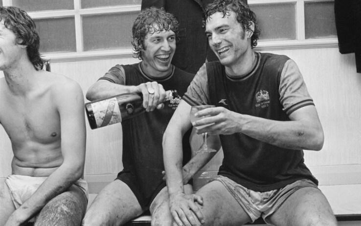 Trevor Brooking (a destra) festeggia con lo champagne l'approdo in finale di Coppa delle Coppe nel 1976
