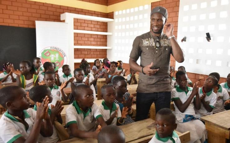 Didier posa coi bambini di una scuola in Costa d'Avorio inaugurata nel 2018