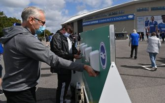 Brighton supporters wearing face coverings use the hand sanitiser provided outside as they arrive ahead of the pre-season friendly football match between Brighton and Hove Albion and Chelsea at the American Express Community Stadium in Brighton, southern England on August 29, 2020. - The game is a 'pilot' event where a small number of fans will be present on a socially-distanced basis. The aim is to get fans back into stadiums in the Premier League by October. (Photo by Glyn KIRK / AFP) (Photo by GLYN KIRK/AFP via Getty Images)