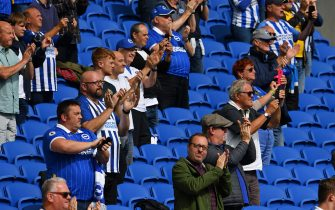 Supporters applaud the teams from their socially-distanced seats ahead of the pre-season friendly football match between Brighton and Hove Albion and Chelsea at the American Express Community Stadium in Brighton, southern England on August 29, 2020. - The game is a 'pilot' event where a small number of fans will be present on a socially-distanced basis. The aim is to get fans back into stadiums in the Premier League by October. (Photo by Glyn KIRK / AFP) (Photo by GLYN KIRK/AFP via Getty Images)