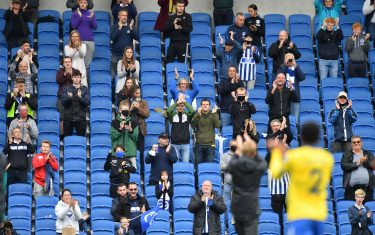 Socially distanced fans applaud players and manager from the stands after the pre-season friendly football match between Brighton and Hove Albion and Chelsea at the American Express Community Stadium in Brighton, southern England on August 29, 2020. - The game is a 'pilot' event where a small number of fans will be present on a socially-distanced basis. The aim is to get fans back into stadiums in the Premier League by October. (Photo by Glyn KIRK / AFP) (Photo by GLYN KIRK/AFP via Getty Images)