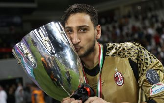 AC Milan's goalkeeper Gianluigi Donnarumma poses with the trophy after winning the Italian Super Cup final match between AC Milan and Juventus in Doha on December 23, 2016.