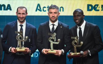 "Juventus' Italian defender Giorgio Chiellini, AS Roma's Serbian defender Alexander Kolarov and Napoli's Senegalese defender Kalidou Koulibaly pose with the award of the best defenders of the year of the Italian Championship Serie A the ""Gran Gala del Calcio"" Italian Football Association (Associazione Italiana Calciatori - IAC) awards ceremony on December 2, 2019, in Milan. (Photo by Miguel MEDINA / AFP) (Photo by MIGUEL MEDINA/AFP via Getty Images)"