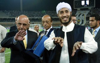 "Adriano Galliani (L) and Al-Saadi Gaddafi make their way through photographers in Tripoli, August 25, 2002. in the VIP box at the ""11 June Stadium"" ahead of the Italian Supercup (Supercoppa Italiana) match Juventus-Parma.