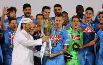 Qatar's Prime Minister, Sheikh Abdullah bin Nasser bin Khalifa al-Thani (L) presents Napoli's Slovak midfielder and captain Marek Hamsik (C) with Italian Super Cup trophy following their football match against Serie A champions Juventus FC, at the Sheikh Jassim Bin Hamad Stadium, in the Qatari capital, Doha on December 22, 2014. The Italian Super Cup was contested between the 2014 Serie A Champions (Juventus) and the 2014 Coppa Italia Holders (Napoli). Napoli defeated Juventus 6-5 on penalties after a draw of 2-2 following extra time. AFP PHOTO / AL-WATAN DOHA / KARIM JAAFAR