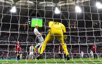 Juventus' Portuguese forward Cristiano Ronaldo (C) heads the ball to score past AC Milan's Italian goalkeeper Gianluigi Donnarumma (R) during their Supercoppa Italiana final between Juventus and AC Milan at the King Abdullah Sports City Stadium in Jeddah on January 16, 2019. (Photo by GIUSEPPE CACACE / AFP)        (Photo credit should read GIUSEPPE CACACE/AFP via Getty Images)
