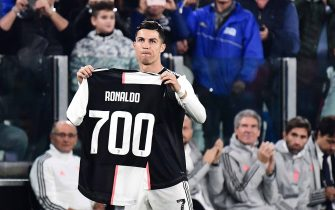 Juventus' Portuguese forward Cristiano Ronaldo holds a jersey bearing his name with the numver 700, after being honoured for having scored 700 goals so far during his career, prior to the Italian Serie A football match Juventus vs Bologna on October 19, 2019 at the Juventus stadium in Turin. (Photo by Marco Bertorello / AFP) (Photo by MARCO BERTORELLO/AFP via Getty Images)