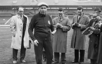 Benfica coach and manager Bela Guttmann (1900 - 1981) with a group of journalists at White City in London, 4th April 1962. He had just accused Tottenham Hotspur of watering the pitch at White Hart Lane, in preparation for their game against Benfica the next day. The match was the second leg semi-final of the European Cup.  (Photo by Keystone/Hulton Archive/Getty Images)