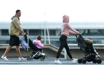 TOPSHOT - Cristiano Ronaldo (L) and his partner Georgina Rodriguez push two strollers as they have a walk with their children in Funchal on March 28, 2020. (Photo by HELDER SANTOS / AFP) (Photo by HELDER SANTOS/AFP via Getty Images)