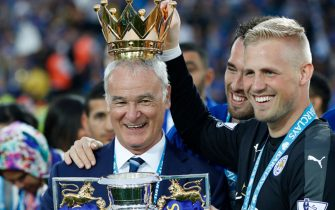 TOPSHOT - Leicester City's Italian manager Claudio Ranieri (L) poses with Leicester City's Austrian defender Christian Fuchs (C) and Leicester City's Danish goalkeeper Kasper Schmeichel with the premier league trophy after winning the league and the English Premier League football match between Leicester City and Everton at King Power Stadium in Leicester, central England on May 7, 2016. / AFP PHOTO / ADRIAN DENNIS / RESTRICTED TO EDITORIAL USE. No use with unauthorized audio, video, data, fixture lists, club/league logos or 'live' services. Online in-match use limited to 75 images, no video emulation. No use in betting, games or single club/league/player publications.  / / AFP PHOTO / ADRIAN DENNIS        (Photo credit should read ADRIAN DENNIS/AFP/Getty Images)