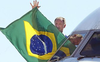 Brazilian soccer team DT Luis Felipe Scolari waves a national flag towards the soccer supporters, from the cockpit of the aircraft that transported the team to Brasilia, 02 July 2002. Thousands of people crowded along the 15 kms (9 mile) route to the presidential palace, where President Fernando Henrique Cardoso is to present the team with the National Order of Merit. AFP PHOTO/VANDERLEI ALMEIDA (Photo by VANDERLEI ALMEIDA / AFP)        (Photo credit should read VANDERLEI ALMEIDA/AFP via Getty Images)