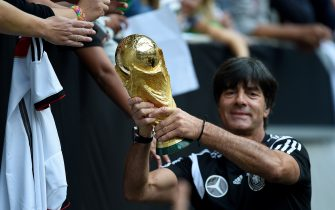 Germany's head coach Joachim Loew shows the world cup trophy during a public training session of the German national football team in Duesseldorf, Germany on September 1, 2014. Germany's squad prepares for the upcoming friendly game against Argentina on September 3, 2014 in Duesseldorf. AFP PHOTO / PATRIK STOLLARZ        (Photo credit should read PATRIK STOLLARZ/AFP via Getty Images)