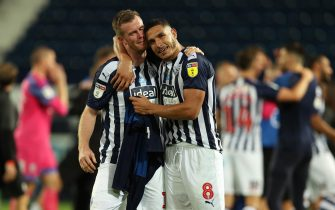 WEST BROMWICH, ENGLAND - JULY 22: Chris Brunt of West Bromwich Albion and Jake Livermore of West Bromwich Albion celebrate promotion  during the Sky Bet Championship match between West Bromwich Albion and Queens Park Rangers at The Hawthorns on July 22, 2020 in West Bromwich, England. Football Stadiums around Europe remain empty due to the Coronavirus Pandemic as Government social distancing laws prohibit fans inside venues resulting in all fixtures being played behind closed doors. (Photo by Matthew Ashton - AMA/Getty Images)