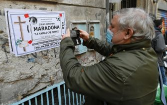 NAPLES, ITALY - NOVEMBER 26: An SSC Napoli fan in mourning for Diego Armando Maradona Death take a picture to a death notice poster for Diego Armando Maradona at Quartieri Spagnoli under Diego Armando Maradona mural on November 26, 2020 in Naples, Italy. Diego Armando Maradona died at 60 after a cardiocirculatory arrest while he was at his house in Tigre, Argentina, where he was spending his convalescence after brain surgery three weeks before. (Photo by Francesco Pecoraro/Getty Images)